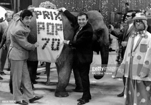 Roger Pierre et JeanMarc Thibault remettant pour plaisanter le prix 'Pop' à un éléphanteau du Cirque d'Hiver à Paris France le 22 septembre 1970