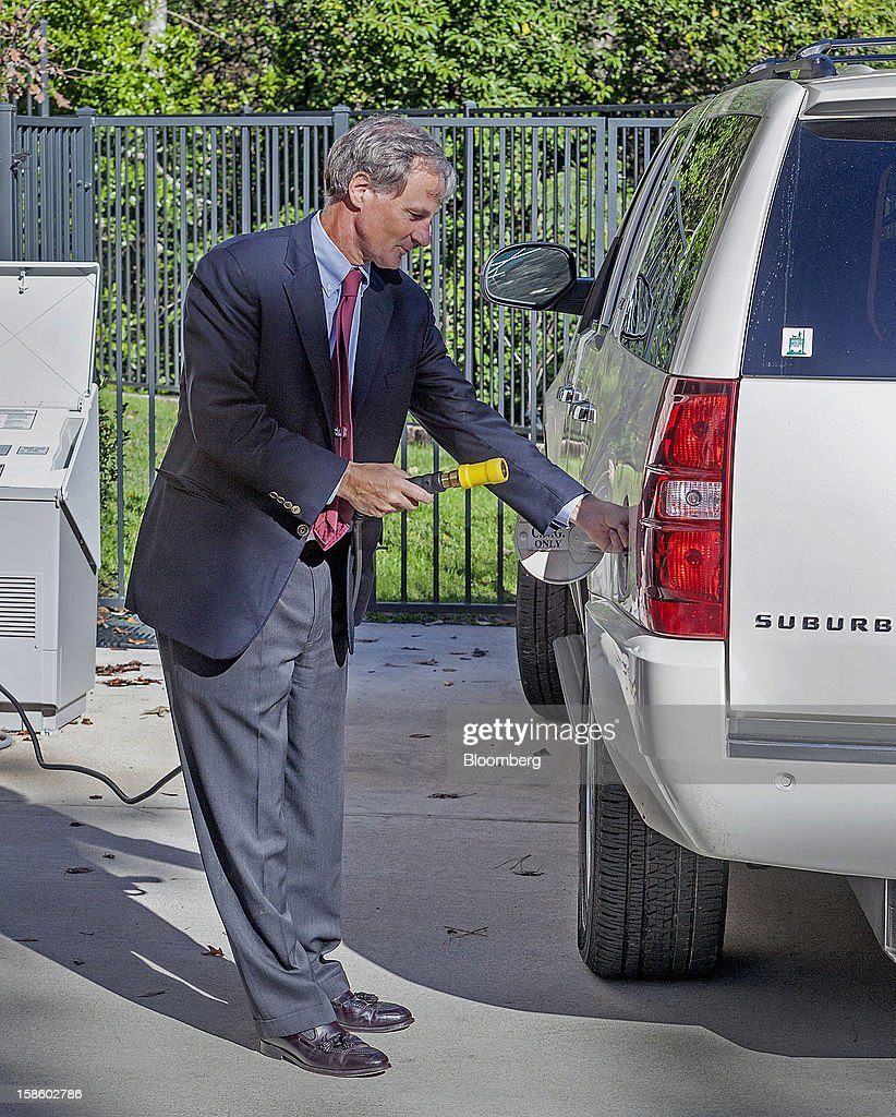 Roger Plank, co-president and chief corporate officer of Apache Corp., fills the tank of his 2011 Chevrolet Suburban sport utility vehicle (SUV), with compressed natural gas (CNG) at a fueling station at his home in Houston, Texas, on Monday, Dec. 17, 2012. Apache Corp. is a gas exploration and production company with operations around the world, including the U.S., U.K., Canada and Argentina. Photographer: Craig Hartley/Bloomberg via Getty Images