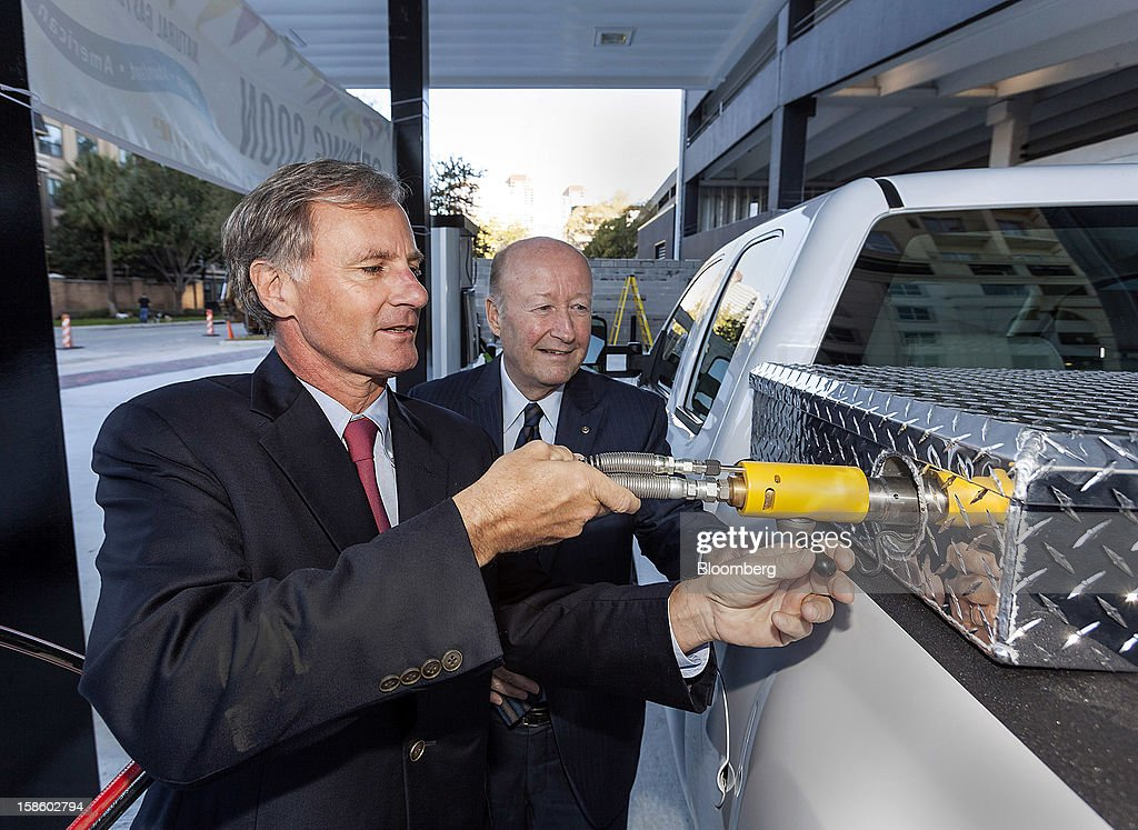 Roger Plank, co-president and chief corporate officer of Apache Corp., left, and Frank R. Chapel, director of national gas transportation fuels at Apache Corp., demonstrate the gas pump at a compressed natural gas (CNG) fueling station in Houston, Texas, on Monday, Dec. 17, 2012. Apache Corp. is a gas exploration and production company with operations around the world, including the U.S., U.K., Canada and Argentina. Photographer: Craig Hartley/Bloomberg via Getty Images