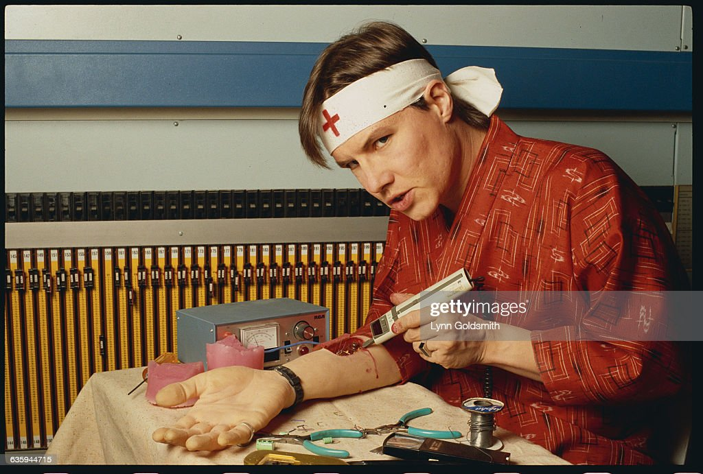 Roger Powell appears to perform surgery on an artificial arm prop.
