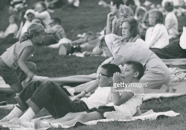 Roger Stevens of 1091 Macon St and James O'Neill of 1070 Macon St relax on the grass and enjoy a snack as they and other children listen to the band...