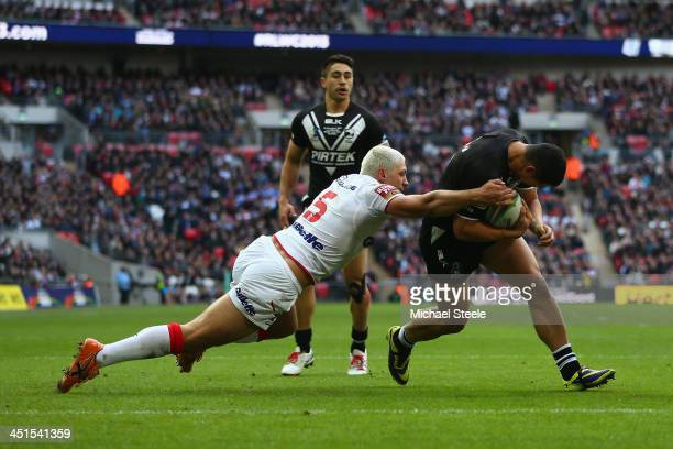 Roger TuivasaScheck of New Zealand forces his way past the challenge of Ryan Hall of England to score his sied opening try during the Rugby League...
