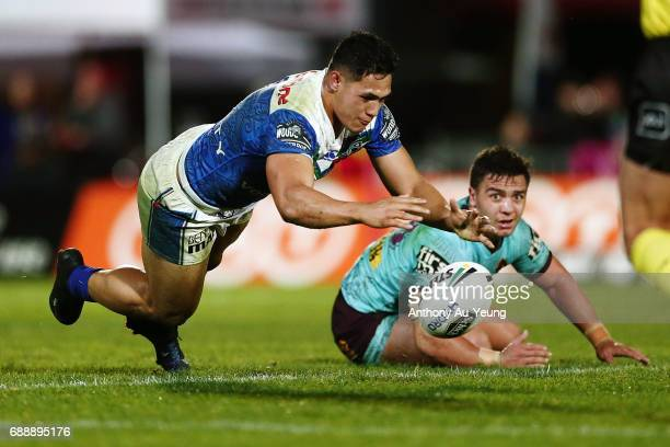 Roger TuivasaSheck of the Warriors claims the loose ball as Kodi Nikorima of the Broncos looks on during the round 12 NRL match between the New...