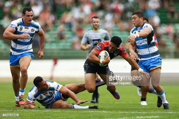 Roger TuivasaSheck of the Warriors is tackled by Ryan James and Ash Taylor of the Titans during the NRL Trial match between the Warriors and the Gold...