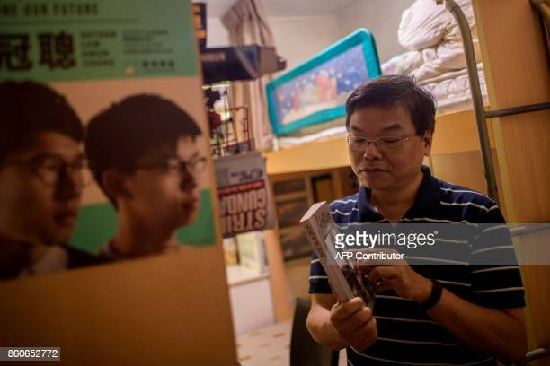 Roger Wong father of jailed prodemocracy activist Joshua Wong holds an original copy of a book which he gave to his son 'People Will Not Forget' a...