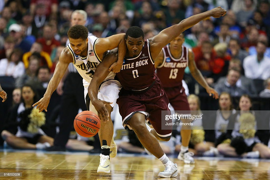 Roger Woods of the Arkansas Little Rock Trojans and PJ Thompson of the Purdue Boilermakers fight for a ball during the first round of the 2016 NCAA...