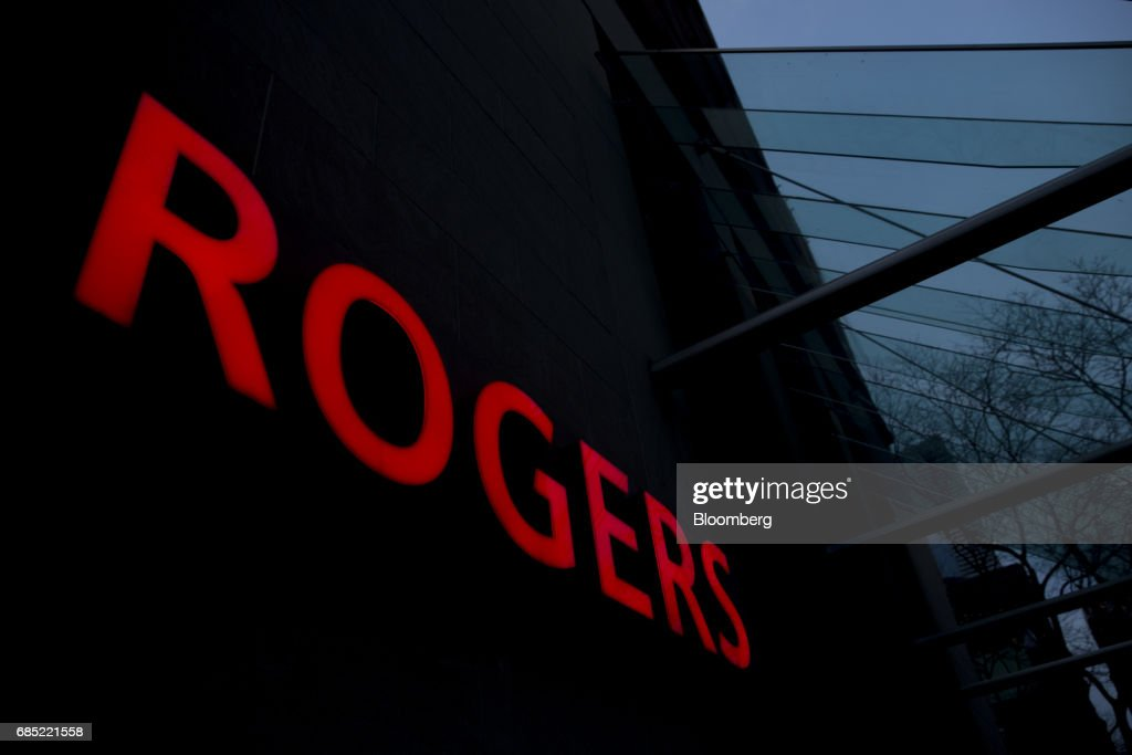 Rogers Communications Inc. signage is illuminated at night on a building in Toronto, Ontario, Canada, on Wednesday, May 17, 2017. Rogers Communications, Canada's largest wireless carrier, is leveraging organic growth in the country's wireless market to expand its subscriber base. Photographer: Brent Lewin/Bloomberg via Getty Images