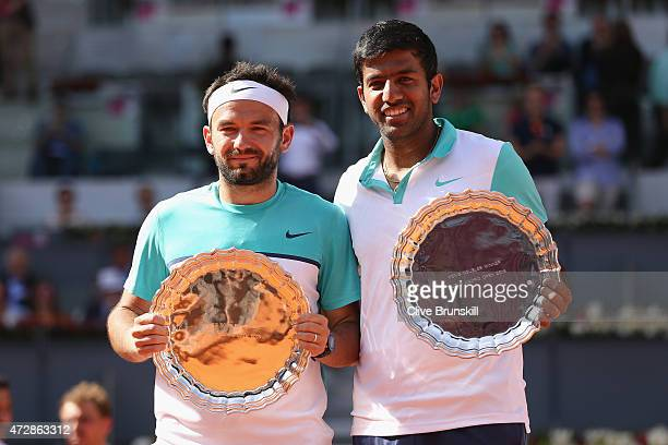 Rohan Bopanna of India and Florin Mergea of Romania hold aloft their winners trophies after their three set victory against Marcin Matkowski of...