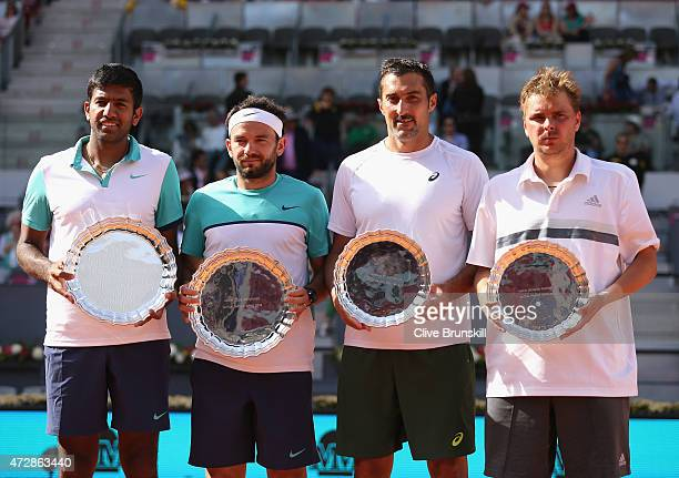 Rohan Bopanna of India and Florin Mergea of Romania hold their winners trophies after their three set victory against Marcin Matkowski of Poland and...