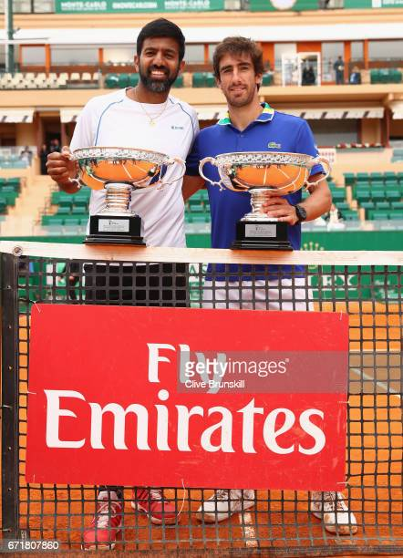 Rohan Bopanna of India and Pablo Cuevas of Uruguay hold their winners trophies after their three set victory against Feliciano Lopez and Marc Lopez...