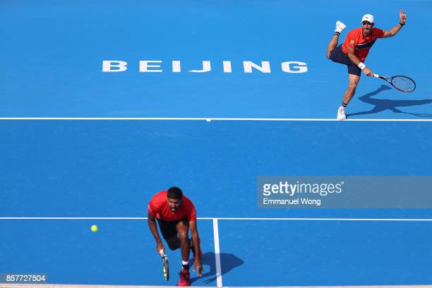 Rohan Bopanna of India and Pablo Cuevas of Uruguay serve against Henri Kontinen of Finland and John Peers of Australia during during their Men's...