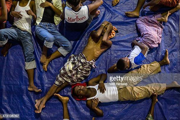 Rohingya and Bangladesh migrants rest inside a shelter on May 13 2015 in Lhoksukon Aceh province Indonesia Boats carrying over 500 of Myanmar's...
