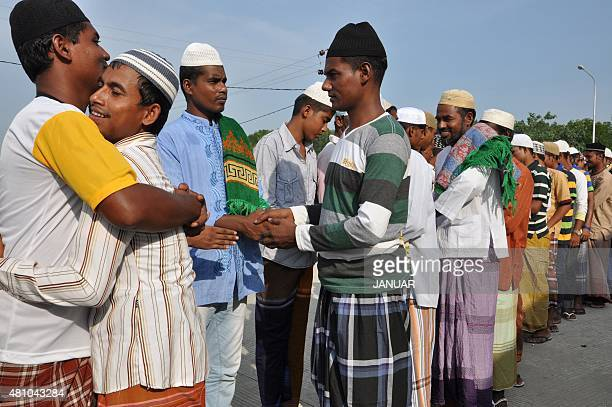 Rohingya and Bangladeshi migrants greet each other after morning prayers celebrating Eid alFitr at a confinement camp for the migrants in Langsa...