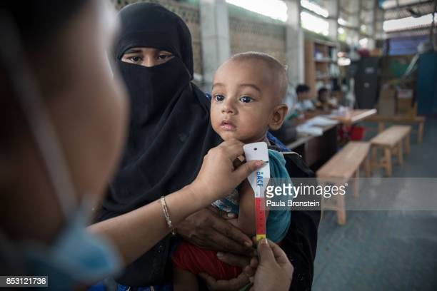 Rohingya boy gets his arm measured to determine how malnourished he is at the Action Against Hunger in the Out Patient Therapeutic program on...