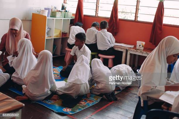 Rohingya boys and girls from various age and level of education join a basic mathematic language class in a community school run by a local NGO on...