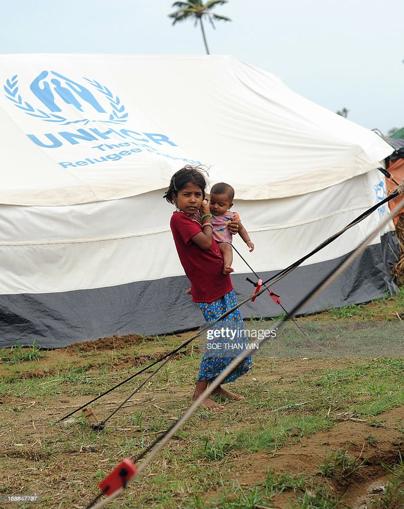 A Rohingya child carries a baby as she stands outside their tent at Ohnedaw Internally displaced people's (IDP) camp, on the outskirts of Sittwe on May 16, 2013, as Cyclone Mahasen caused heavy rains and strong winds to lash Myanmar's northwest coast, home to tens of thousands of displaced Muslim Rohingya. Cyclone Mahasen ripped into the Bangladeshi coast on May 16 as hundreds of thousands of people hunkered down in evacuation shelters, including in a region of Myanmar torn by communal unrest. AFP PHOTO / Soe Than WIN