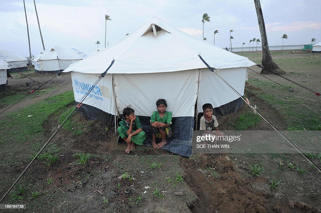 Rohingya children sit beside a relief tent as a freshly dug drainage ditch surrounds the tent at the Ohnedaw Internally Displaced Persons (IDP) camp on the outskirts of Sittwe on May 15, 2013, as Cyclone Mahasen heads towards landfall. Hundreds of thousands of people in Bangladesh and Myanmar were ordered to evacuate Wednesday as a cyclone bore down on coastal areas home to flood-prone refugee camps for victims of sectarian unrest.