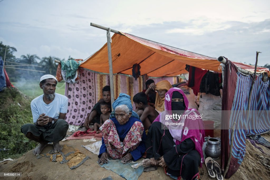 A Rohingya family sits under a makeshift tent at a refugee camp in Cox's Bazar, Bangladesh, on Tuesday, Sept. 12, 2017. Myanmar's leader Aung San Suu Kyi is under attack over her response to a fresh round of violence that has seen more than 145,000 minority Rohingya Muslims flee into neighboring Bangladesh since last month. Photographer: Ismail Ferdous/Bloomberg via Getty Images