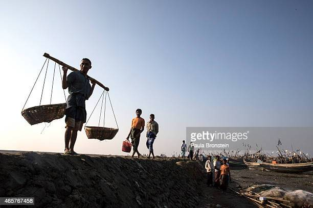 Rohingya fishermen carry supplies wait for the tide to come in on a boat jetty March 7 2015 in the village of Thae Chaung where the Rohingya have...