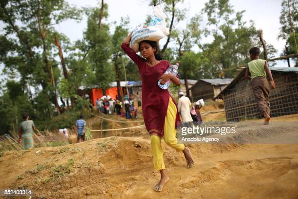 Rohingya girl carries a sack at a makeshift camp in Teknaff Bangladesh on September 23 2017 Violence erupted in Myanmars Rakhine state on Aug 25 when...