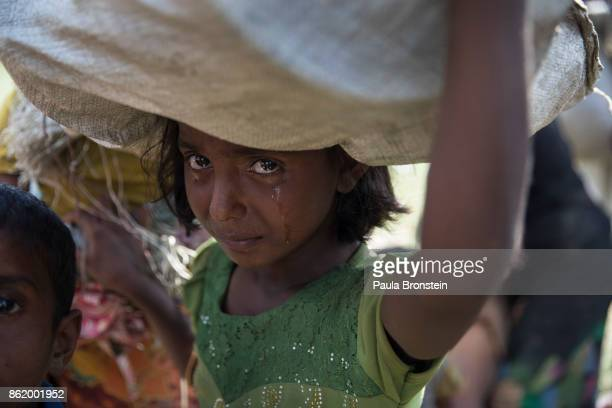Rohingya girl cries as refugees fleeing from Myanmar cross a stream in the hot sun on a muddy rice field on October 16 2017 near Palang Khali Cox's...