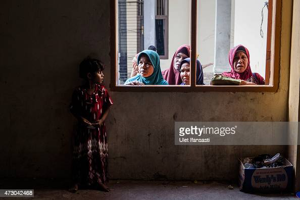 Rohingya girl migrant stands as look out through the window at a shelter on May 12 2015 in Lhoksukon Aceh province Indonesia Boats carrying over 500...