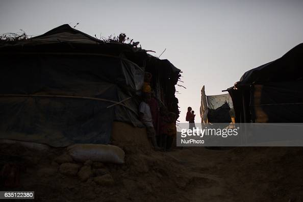 A Rohingya girl stands holding a child at Kutupalong Refugee Camp Cox's Bazar Bangladesh on February 13 2017 After attacks by Rohingya militants on...