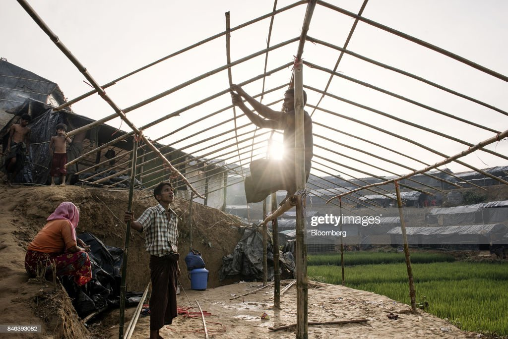 A Rohingya man builds a hut at a newly set-up refugee camp at Balukhali in Cox's Bazar, Bangladesh, on Tuesday, Sept. 12, 2017. Myanmar's leader Aung San Suu Kyi is under attack over her response to a fresh round of violence that has seen more than 145,000 minority Rohingya Muslims flee into neighboring Bangladesh since last month. Photographer: Ismail Ferdous/Bloomberg via Getty Images