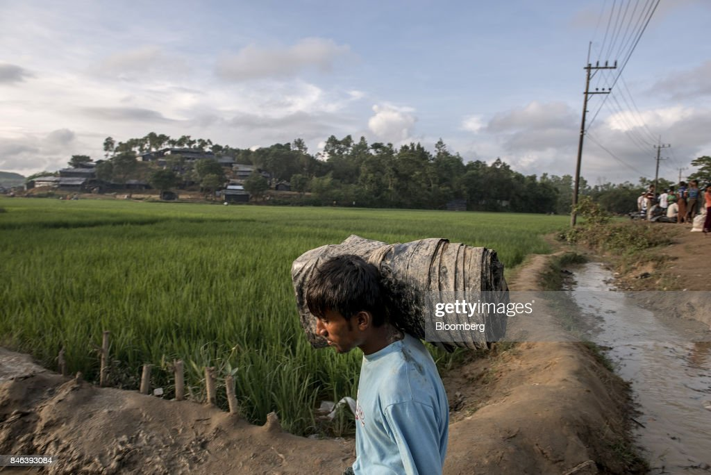A Rohingya man carries a rolled up tarp past rice paddies near a newly set-up refugee camp at Balukhali in Cox's Bazar, Bangladesh, on Tuesday, Sept. 12, 2017. Myanmar's leader Aung San Suu Kyi is under attack over her response to a fresh round of violence that has seen more than 145,000 minority Rohingya Muslims flee into neighboring Bangladesh since last month. Photographer: Ismail Ferdous/Bloomberg via Getty Images