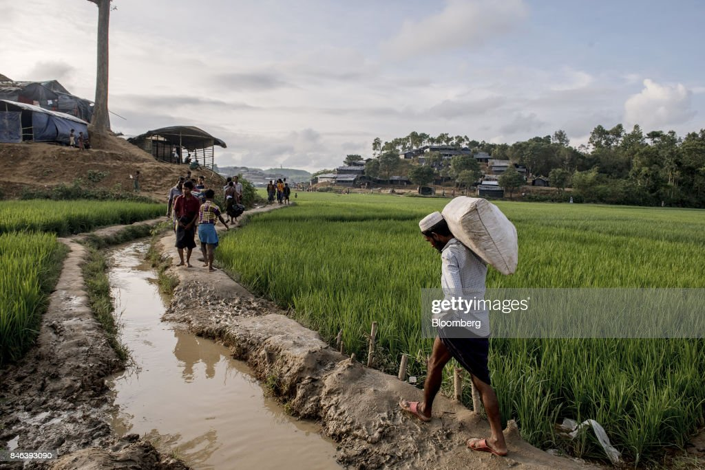A Rohingya man carries a sack of food rations past rice paddies near a newly set-up refugee camp at Balukhali in Cox's Bazar, Bangladesh, on Tuesday, Sept. 12, 2017. Myanmar's leader Aung San Suu Kyi is under attack over her response to a fresh round of violence that has seen more than 145,000 minority Rohingya Muslims flee into neighboring Bangladesh since last month. Photographer: Ismail Ferdous/Bloomberg via Getty Images