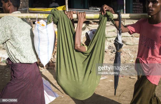 COX'S BAZAR BANGLADESH SEPTEMBER 27 Rohingya men carry a woman with a stick at the Balukhali makeshift camp in Cox's Bazar Bangladesh on September 27...
