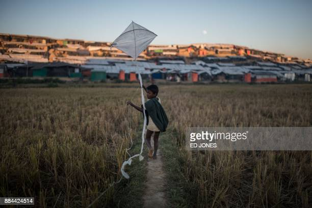 A Rohingya migrant boy runs with a kite through the Thankhali refugee camp in Cox's Bazar on December 2 2017 Rohingya are still fleeing into...