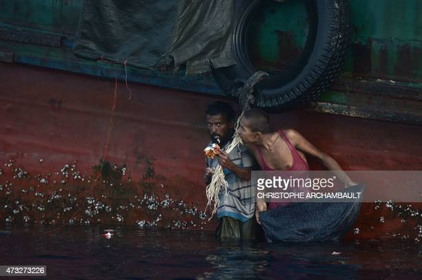 A Rohingya migrant eats food dropped by a Thai army helicopter after he jumped to collect the supplies at sea from a boat drifting in Thai waters off...