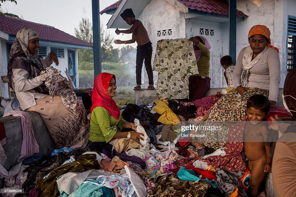 Rohingya migrant women collect used clothes at a temporary shelter on May 18, 2015 in Kuala Langsa, Aceh province, Indonesia. Hundreds of Myanmar's Rohingya refugees arrived in Indonesia on May 15, many requiring medical attention. Thousands more are believed to still be stranded at sea reportedly with no country in the region willing to take them in. Myanmar's Rohingya Muslim community have long been persecuted and marginalized by Myanmar's mostly Buddhist population.