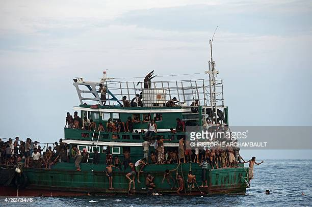 Rohingya migrants bring back food supplies dropped by a Thai army helicopter after jumping to collect them at sea from a boat drifting in Thai waters...