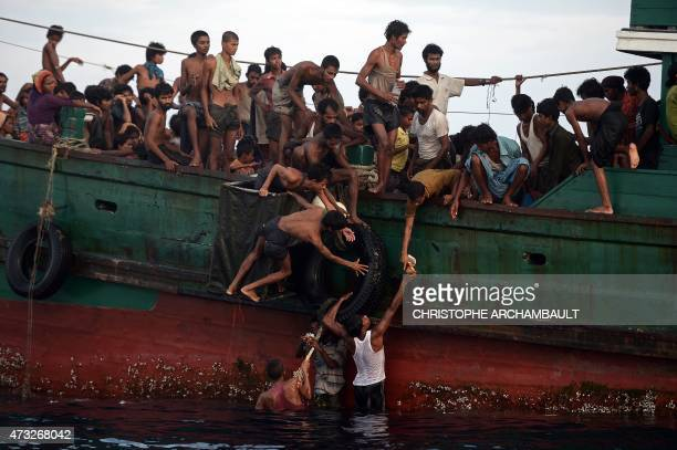 Rohingya migrants pass food supplies dropped by a Thai army helicopter to others aboard a boat drifting in Thai waters off the southern island of Koh...