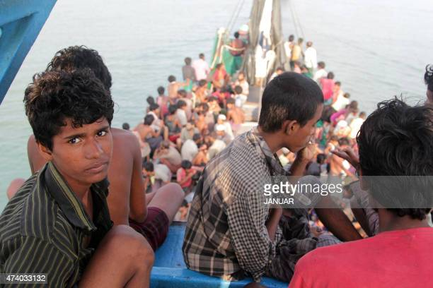 Rohingya migrants sit in a boat as they're towed closer to land by fishermen off the coast near the city of Geulumpang in Indonesia's East Aceh...