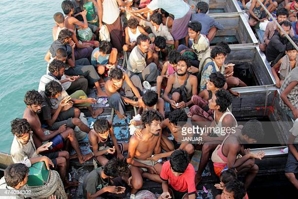 Rohingya migrants sit in their boat as they are towed closer to land by Acehnese fishermen off the coast near the city of Geulumpang in Indonesia's...