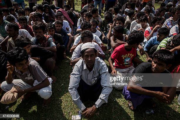 Rohingya migrants sit on the ground after arriving at the port in Julok village on May 20 2015 in Kuta Binje Aceh Province Indonesia Hundreds of...