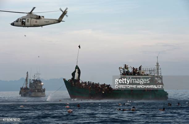 Rohingya migrants swim to collect food supplies dropped by a Thai army helicopter after they jumped from a boat drifting in Thai waters off the...