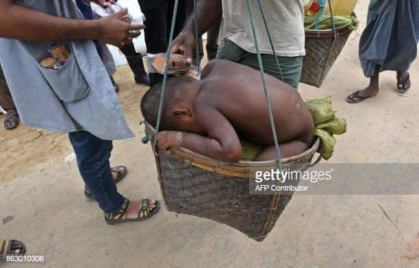 A Rohingya Muslim child sleeps as he is carried by his father as he walks from the 'noman's land' between Myanmar and Bangladesh into Palongkhali in...
