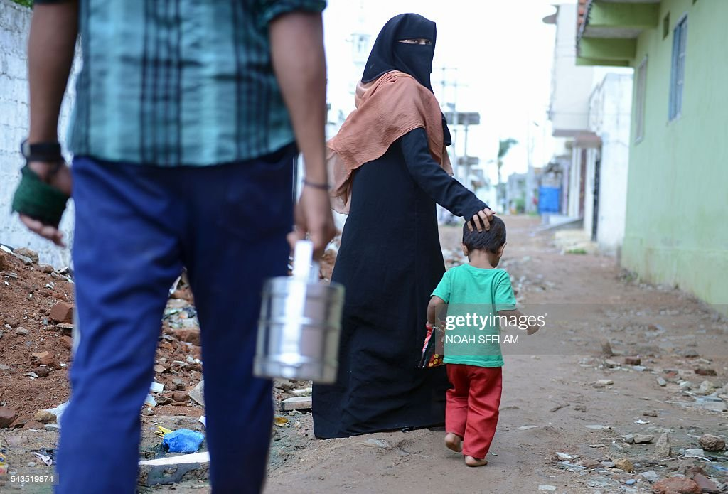 A Rohingya Muslim family walk to leave a refugee camp on their way to work as day labourers in the old city of Hyderabad on June 29, 2016. More than 1,200 Rohingya Muslims fleeing sectarian violence in Myanmar have settled in crammed quarters and makeshift shelters in the old city in Hyderabad, in the southern Indian state of Telangana. The Rohingyas have been described by the United Nations as one of the world's most persecuted minorities. They have fled Myanmar in their thousands in recent years as hardline monks and Buddhist nationalists fiercely oppose moves to recognise them as an official minority and insist on calling them 'Bengalis' -- shorthand for illegal migrants from the border with Bangladesh. / AFP / NOAH