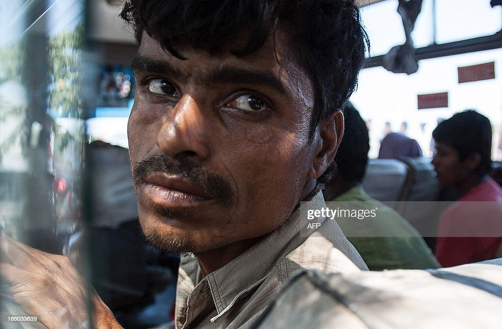 A Rohingya Muslim from Myanmar sits inside a bus as authority remove them to a dentention center in Banda Aceh on April 8, 2013, after stranded on remote island Pulo Aceh. Indonesian police on April 7 detained 80 Rohingya Muslims from Myanmar on a remote island off Sumatra after they had got lost attempting to reach Malaysia, an official said. It was the latest boatload of Rohingya to arrive on the shores of Indonesia, as thousands flee Myanmar after tensions between Muslims and Buddhists exploded in their home state of Rakhine last year.