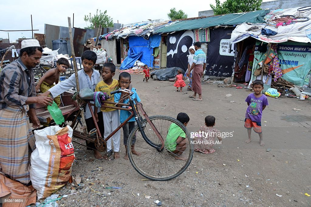 A Rohingya Muslim man and children sort through scrap collected from a dump yard at their refugee camp in the old city of Hyderabad on June 29, 2016. More than 1,200 Rohingya Muslims fleeing sectarian violence in Myanmar have settled in crammed quarters and makeshift shelters in the old city in Hyderabad, in the southern Indian state of Telangana. The Rohingyas have been described by the United Nations as one of the world's most persecuted minorities. They have fled Myanmar in their thousands in recent years as hardline monks and Buddhist nationalists fiercely oppose moves to recognise them as an official minority and insist on calling them 'Bengalis' -- shorthand for illegal migrants from the border with Bangladesh. / AFP / NOAH