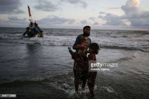COX'S BAZAR BANGLADESH SEPTEMBER 13 A Rohingya Muslim man fled from ongoing military operations in Myanmars Rakhine state passes a child to a girl...
