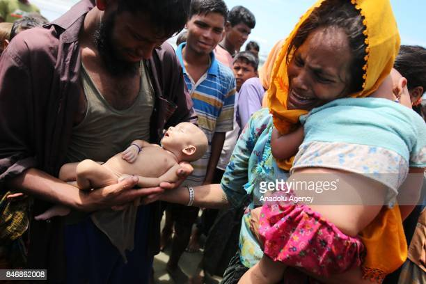 Rohingya Muslim man holds his infant son who died when the boat they were traveling in capsized just before reaching the shore of the Bay of Bengal...