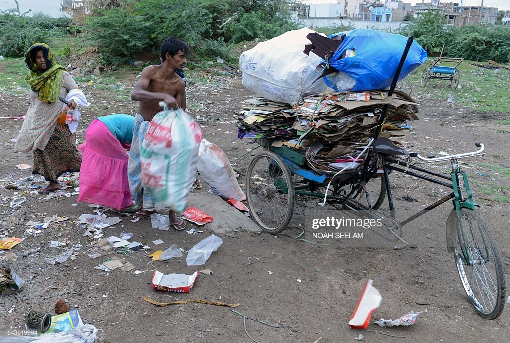 Rohingya Muslim man Mohammed Siddiq (centre L) and members of his family collect items at a dump yard that they can sell at scrap market in the old city of Hyderabad on June 29, 2016. More than 1,200 Rohingya Muslims fleeing sectarian violence in Myanmar have settled in crammed quarters and makeshift shelters in the old city in Hyderabad, in the southern Indian state of Telangana. The Rohingyas have been described by the United Nations as one of the world's most persecuted minorities. They have fled Myanmar in their thousands in recent years as hardline monks and Buddhist nationalists fiercely oppose moves to recognise them as an official minority and insist on calling them 'Bengalis' -- shorthand for illegal migrants from the border with Bangladesh. / AFP / NOAH