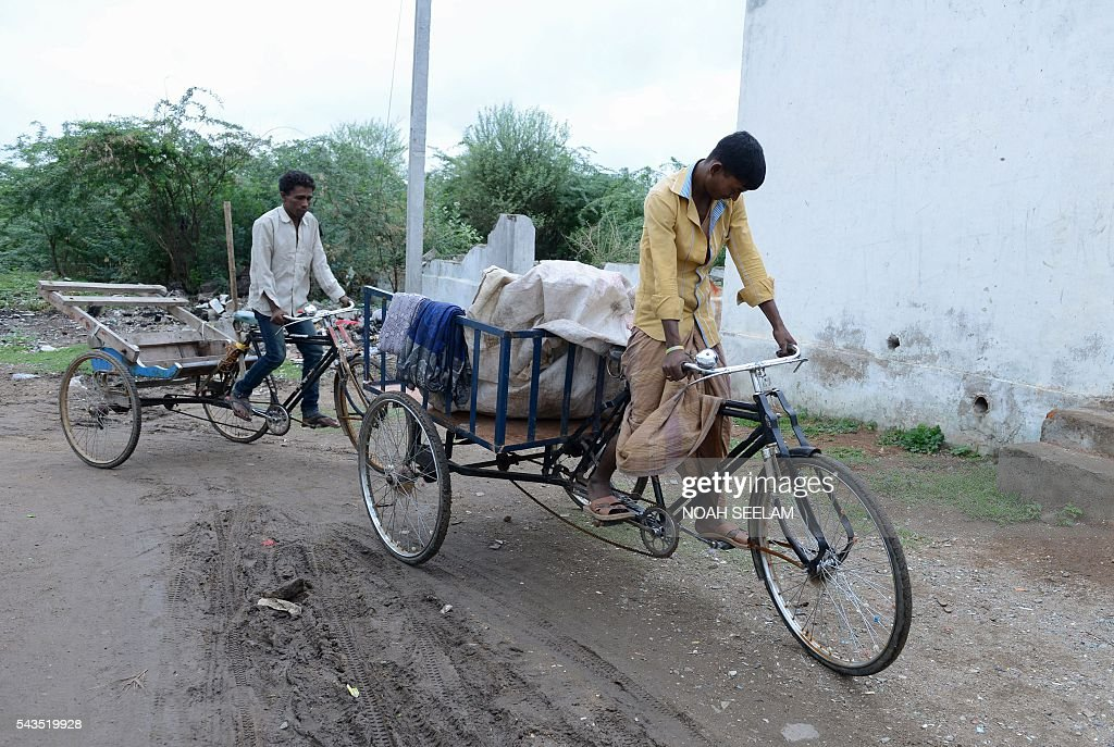 Rohingya Muslim men ride their tricycles on their way to a dump yard to collect items to sell at a scrap market next to their refugee camp in the old city of Hyderabad on June 29, 2016. More than 1,200 Rohingya Muslims fleeing sectarian violence in Myanmar have settled in crammed quarters and makeshift shelters in the old city in Hyderabad, in the southern Indian state of Telangana. The Rohingyas have been described by the United Nations as one of the world's most persecuted minorities. They have fled Myanmar in their thousands in recent years as hardline monks and Buddhist nationalists fiercely oppose moves to recognise them as an official minority and insist on calling them 'Bengalis' -- shorthand for illegal migrants from the border with Bangladesh. / AFP / NOAH
