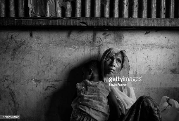 COX'S BAZAR BANGLADESH OCTOBER 24 Rohingya Muslim refugee Ambia Khatun holds her grandson Muhammed as they rest inside a local school being used as a...