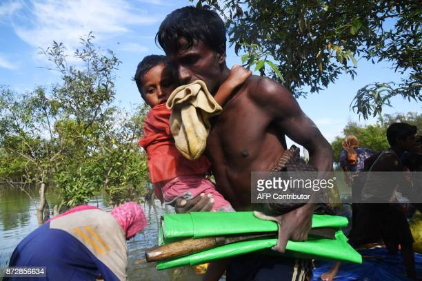 A Rohingya Muslim refugee carries a child as he walks out of a makeshift raft after sailing to cross the Naf River and enter in Bangladesh at Sabrang...